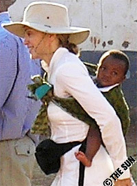 Певица Мадонна с усыновленным ребенком в слинге